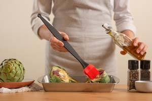 Coat the tips of artichokes with olive oil